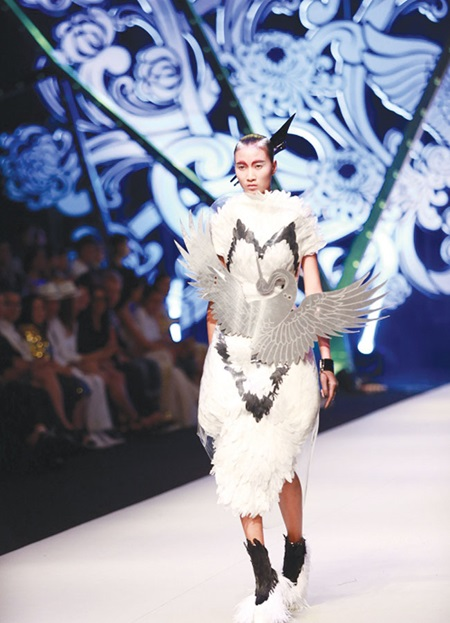A model presents a creation by Tien Truyen, whose collection was inspired by the crane. Truyen reacts when he was announced as winner of Vietnam Project Runway 2015. — Photos vnexpress.net