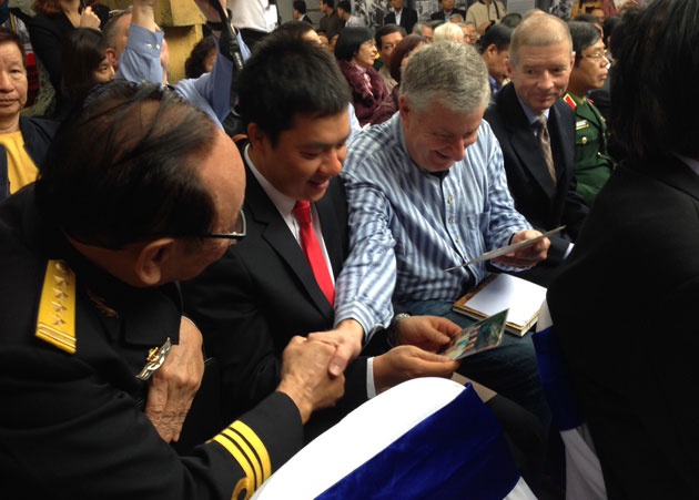 American POW Robert P. Chenoweth and former Hoa Lo prison warden Tran Trong Duyet looking at photos and recalling their past memories (Photo: Tuyet Loan)