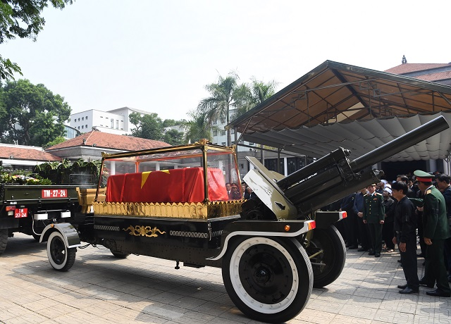 Former Party General Secretary Do Muoi's flag-draped coffin is escorted from the National Funeral Hall to his last resting place in his home town on the outskirts of Hanoi.