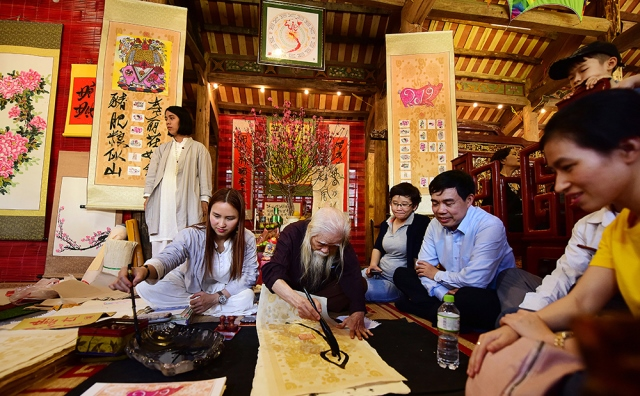 People ask for parallel sentences from calligraphy scholars to bring home and hang to bring luck to their families in the new year.