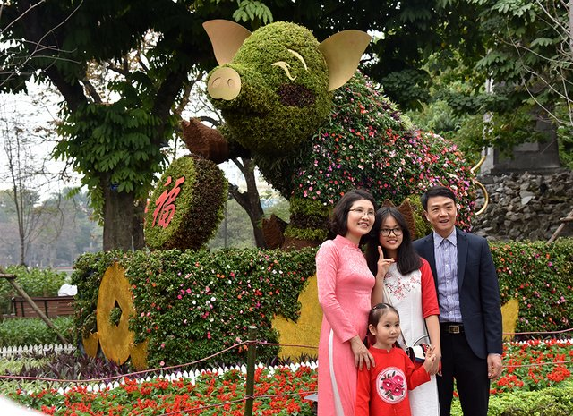 A pig model made from flowers and green trees impressing tourists around Hoan Kiem Lake.
