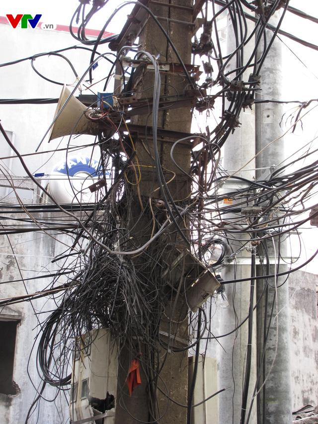 Nguy cơ cháy nổ từ những tổ nhện trên đường phố Hà Nội - Ảnh 1.