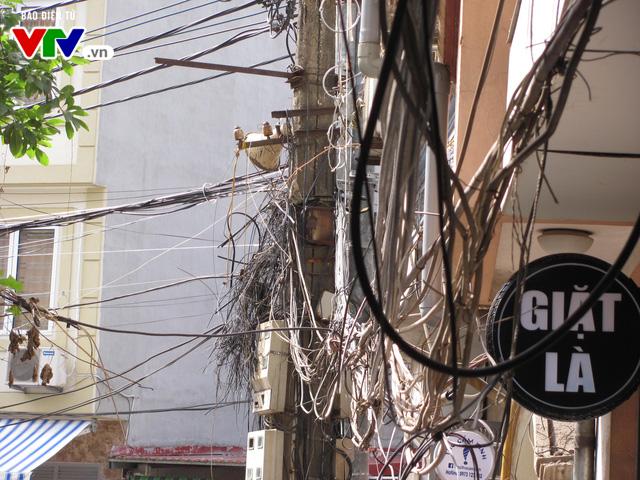 Những cây cột điện, mạng dây điện có nguy cơ cháy nổ cao trên đường phố Hà Nội - Ảnh 4.