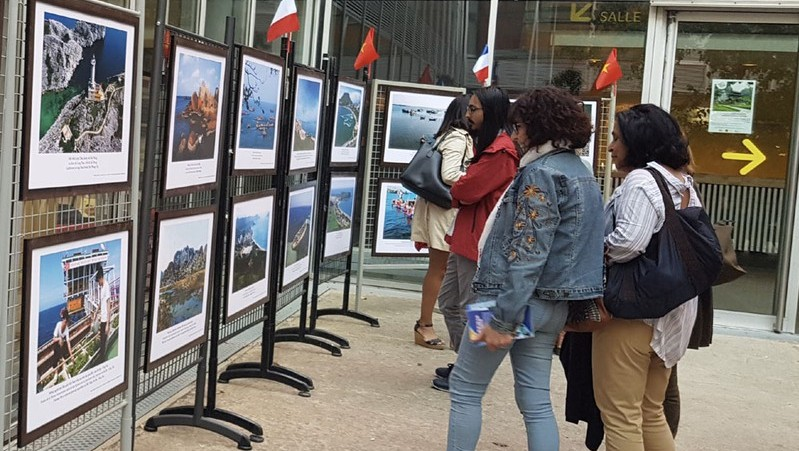 French visitors admiring photos on display at an exhibition highlighting Vietnam's sea-based tourism. (Photo: VOV)