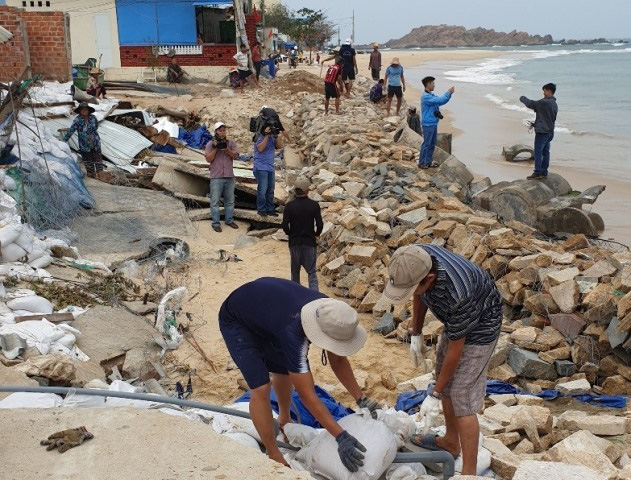 Locals in Nhon Hai commune, Quy Nhon city strengthen a sea embankment section to brace against Storm Nakri. (Photo: NDO/Cat Hung)
