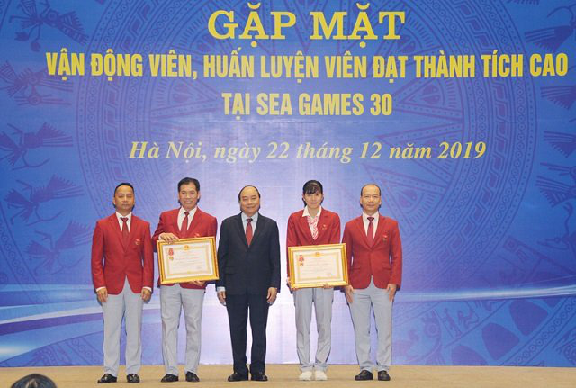 PM Nguyen Xuan Phuc (C) presents the first-class Labour Order to the Vietnamese sports delegation to SEA Games 30 and swimmer Nguyen Thi Anh Vien (second from right). (Photo: NDO/Tran Hai)