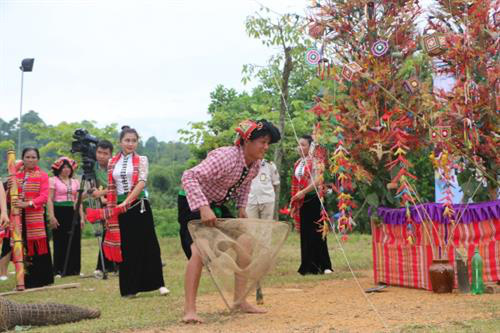 A shaman simulates the act of catching shrimp using a bamboo trap (Photo: dantocmiennui.vn)