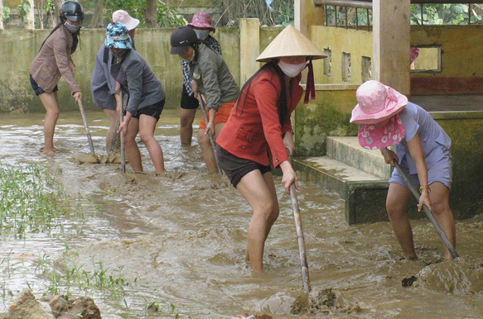 Teachers in the Quang Ninh floodplain in Quang Binh Province clearing the mud at a local school to welcome back students after the flooding recedes. (Photo: NDO/Huong Giang)