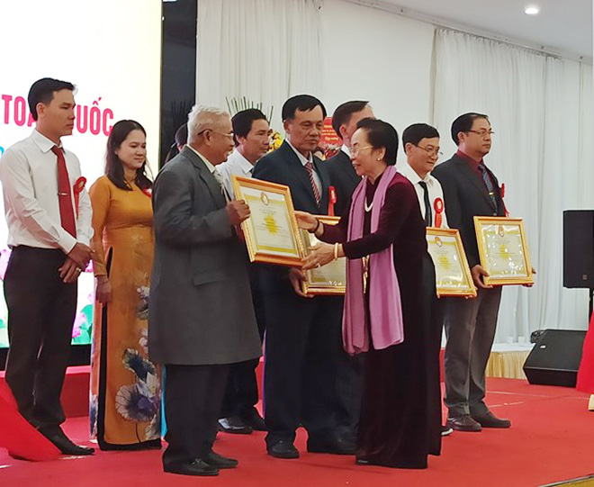 Former Vice President Nguyen Thi Doan, President of the Vietnam Association for Promoting Education, presents certificates of merits to representatives of exemplary learning models. (Photo: qdnd.vn)