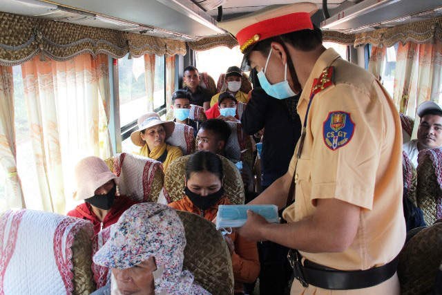 A policeman in Dak Lak Province distributes free medical masks to people traveling by coach on Ho Chi Minh Highway. (Photo: NDO)