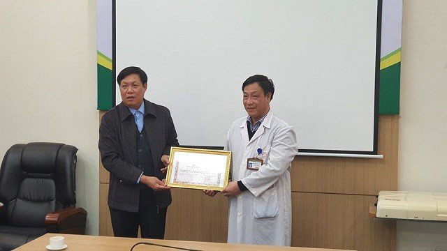 Deputy Minister of Health Do Xuan Tuyen (L) presents a Certificate of Merit to the National Hospital of Tropical Diseases. (Photo: NDO/Hai Ngo)