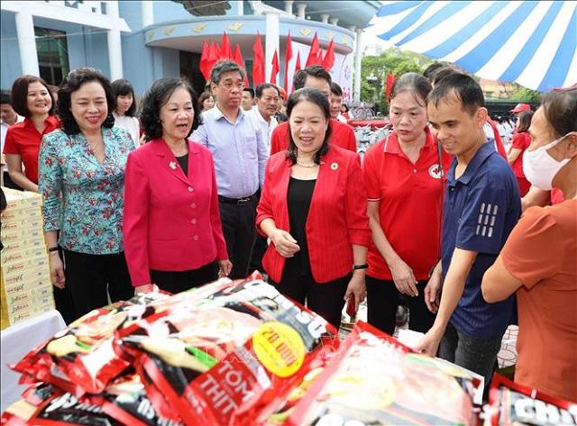 Politburo member Truong Thi Mai (in red coat, left) visits a booth at the humanitarian market. (Photo: VNA)