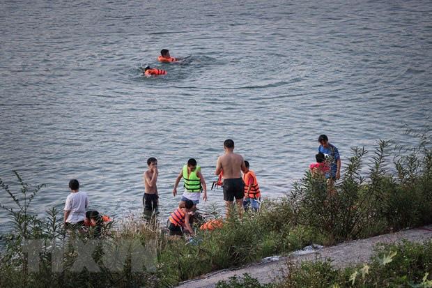 Người lớn lẫn trẻ em xuống tắm sông Đà trong những ngày nắng nóng, bất chấp những biển cảnh báo nguy hiểm được các đơn vị chức năng cắm trên bờ sông. (Ảnh: TTXVN)
