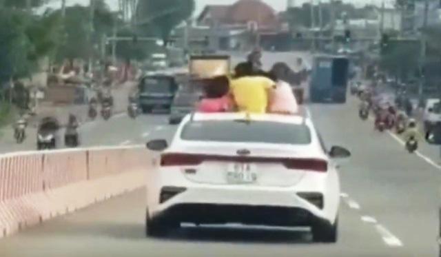 3 trẻ nhỏ ngồi chơi trên nóc ô tô đang lao vun vút: Vừa xem, vừa run - Ảnh 1.