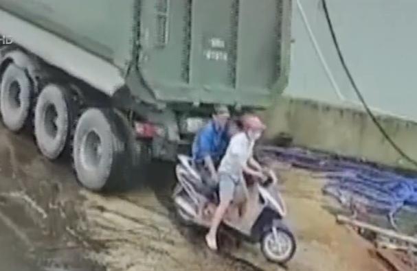 Xe ben lùi xe bất cẩn, hai người ngồi trên xe máy thoát chết trong gang tấc - Ảnh 1.