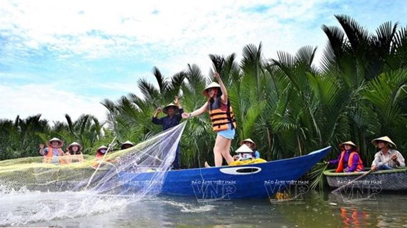 A visitor learns how to use a fishing net during a boat tour to Cam Thanh coconut village in Quang Nam province. (Photo: Vietnam Pictorial)