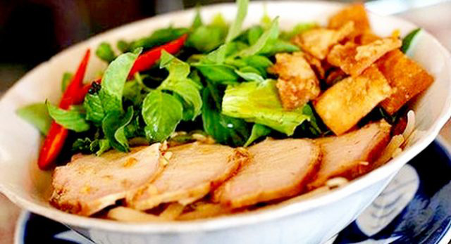 A bowl includes fresh rice noodles, slices of barbecued pork, bean sprouts, lettuce, and aromatic herbs.