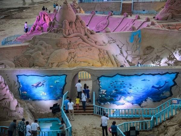 Du khách thưởng thức những tác phẩm điêu khắc từ cát. (Nguồn: AFP/TTXVN)
