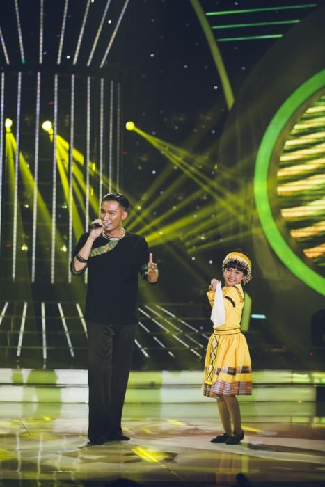 Chí Thiện và bé Bảo An mặc trang phục dân tộc, sắm vai ca sĩ Phạm Anh Khoa và Ngọc Khuê, biểu diễn Trước ngày hội bắn