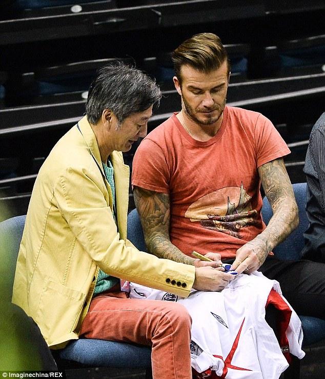Beckham ký tặng một người hâm mộ địa phương trong chuyến thăm Macau, Trung Quốc.