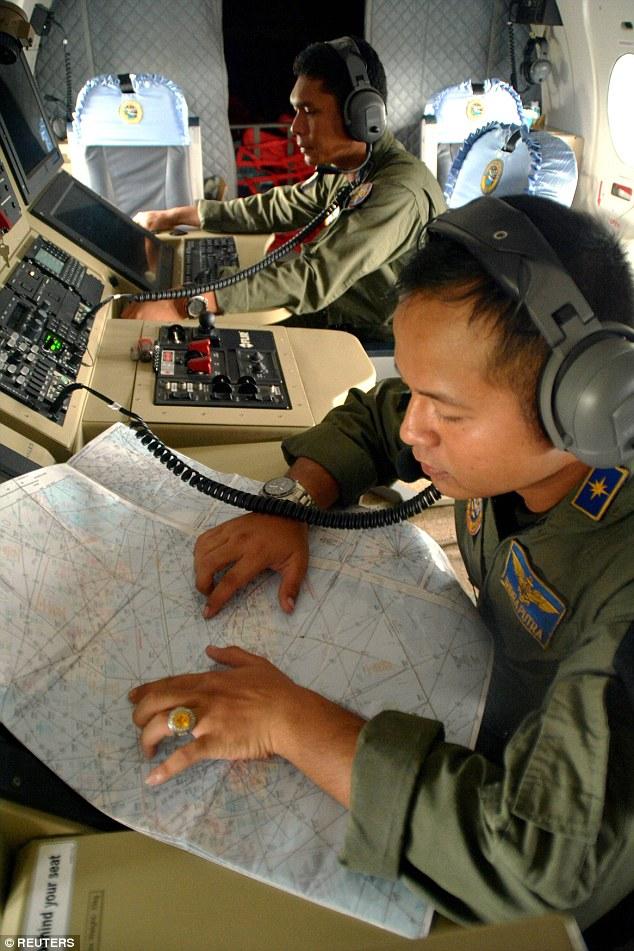 Hai thành viên của một đơn vị Hải quân của Indonesia hỗ trợ việc tìm kiếm máy bay.