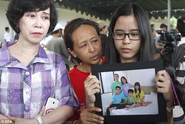 Người thân của một gia đình cầm ảnh khi đang chờ đợi tin tức ở sân bay Juanda Airport, Surabaya, Indonesia.
