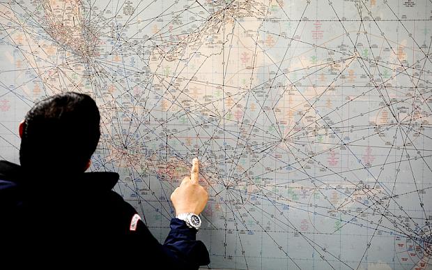 Một nhân viên tìm kiếm cứu hộ của Indonesia không rời khỏi mắt tấm bản đồ.