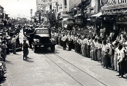 Nhân dân phất cờ, tung hoa, reo mừng, chào đón đoàn quân tiến về giải phóng Thủ đô ngày 10/10/1954. Ảnh tư liệu/ Chinhphu.vn