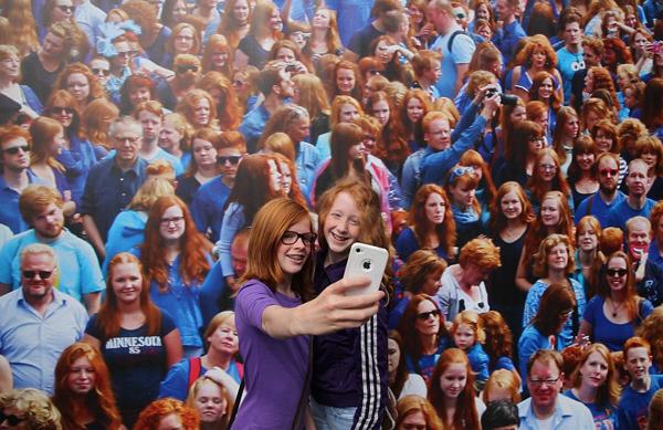 Hai cô bé tóc đỏ tranh thủ tự sướng trước bức hình lớn chụp những người tham gia lễ hội từ năm trước. (Nguồn: Theo Dailymail)