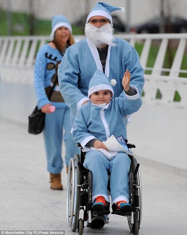 Một em bé ngồi xe lăn cùng bố mặc áo ông già Noel tham dự Santa Stroll.