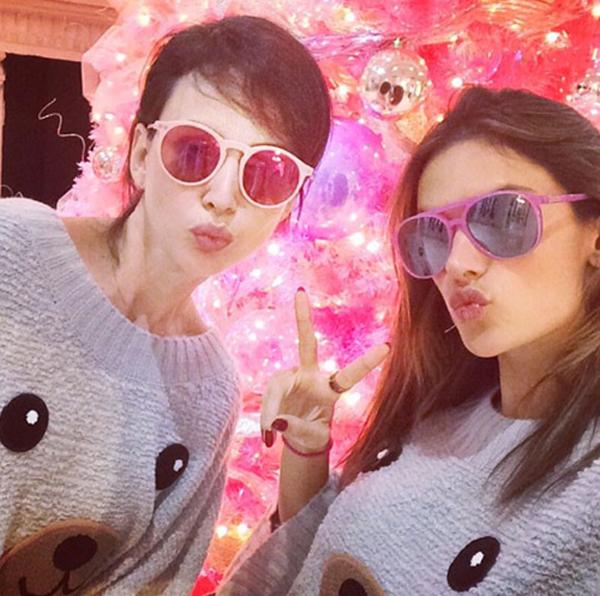 """Còn siêu mẫu Alessandra Ambrosio Alessandra (phải) chọn cách đi dạo, mua sắm cùng bạn thân vào dịp lễ. Cô nhí nhảnh """"tự sướng"""" cùng bạn bên cây thông Noel. Cả hai còn mặc áo đôi với hình ảnh mặt gấu dễ thương."""