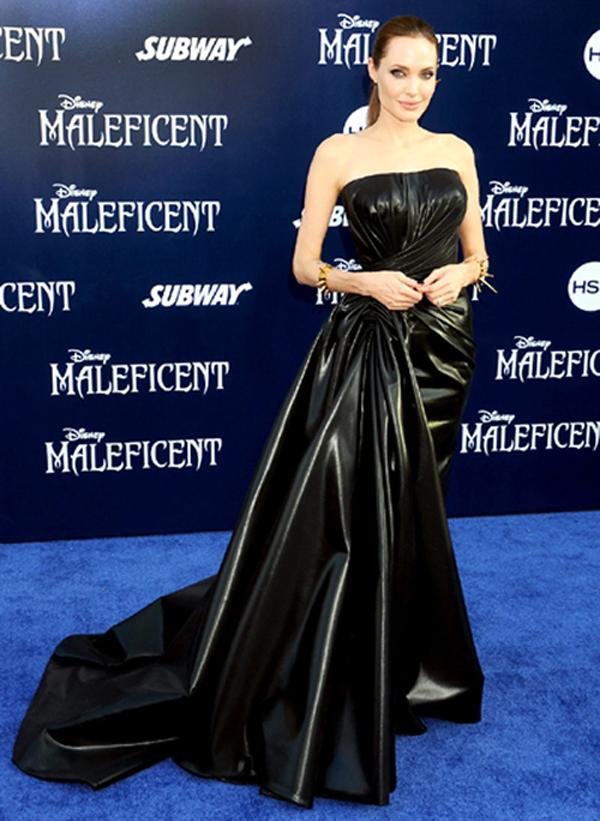 """Trong buổi ra mắt bộ phim """"Maleficent"""", Angelina Jolie trở nên ấn tượng và nổi bật trong bộ váy da đen dài, bóng bẩy, một thiết kế của thương hiệu Versace. Đi kèm với chiếc váy còn là bộ vòng đinh nhọn màu vàng, khiến người xem gợi nhớ ngay ra nhân vật """"tiên hắc ám"""" mà cô vào vai."""
