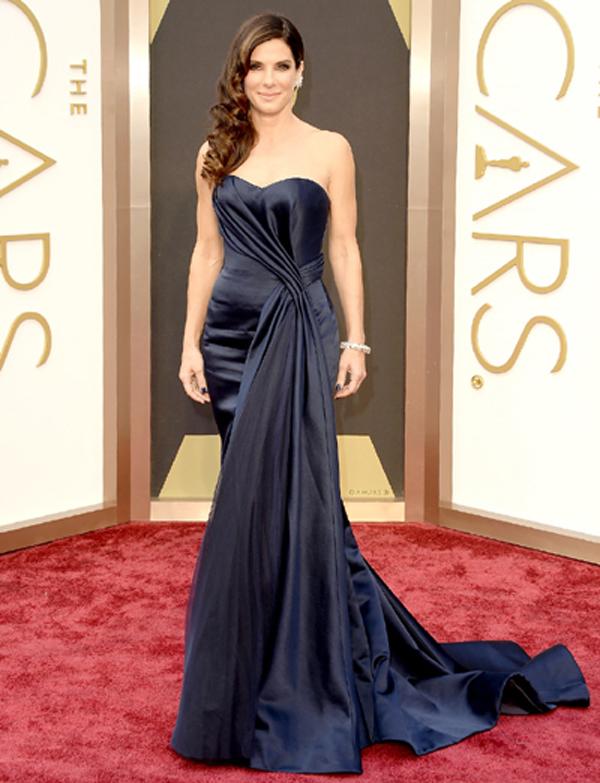 """Trên thảm đỏ của Lễ trao giải Oscar năm nay, Sandra Bullock cũng không kém phần quyến rũ trong chiếc đầm dài màu xanh hải quân, một thiết kế của Alexander McQueen. Chiếc đầm cúp ngực, nổi bật với phần hông được cách điệu, kết hợp cùng trang sức của Lorraine Schwartz càng khiến nữ diễn viên """"Gravity"""" trở nên sang trọng hơn."""