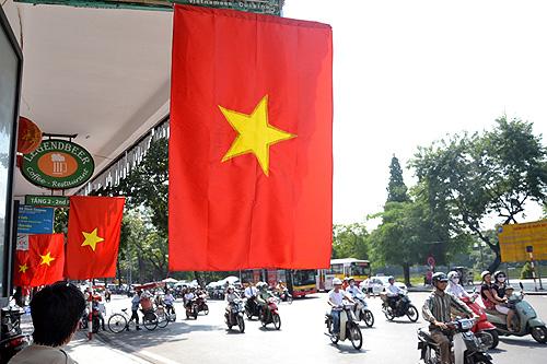 Nhà dân, cửa hàng trên các tuyến phố đồng loạt treo cờ Tổ quốc khiến phố phường trở nên rực rỡ (Ảnh: Thanh Niên Online)
