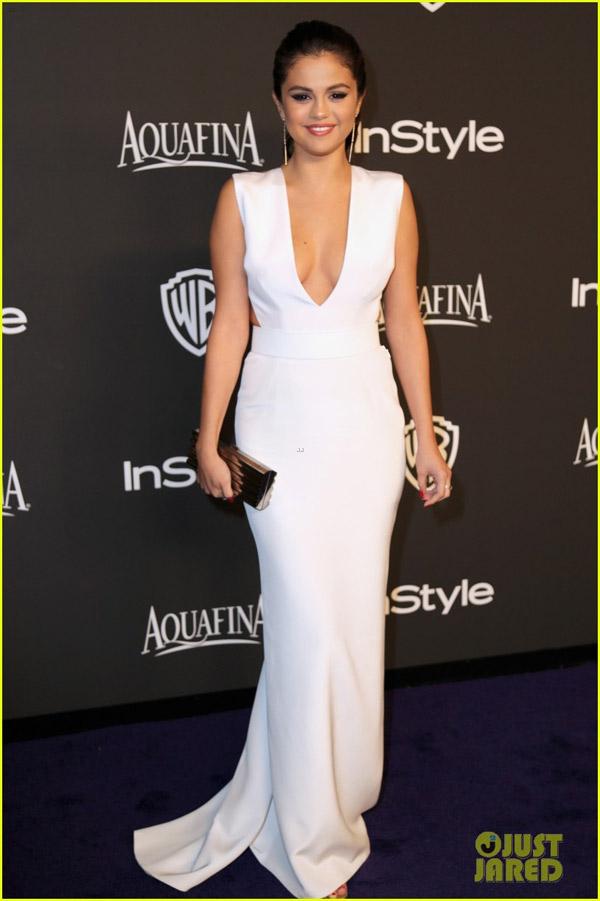 Selena diện chiếc váy xẻ ngực màu trắng, trang điểm khá đậm.