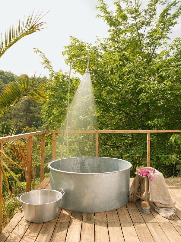 Sự kết hợp giữa bồn tắm kim loại và sàn gỗ trên sân thượng tạo cảm giác hài hòa, tươi mới với không gian đầy cây cối xung quanh.