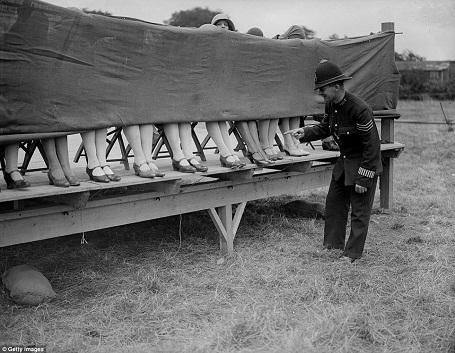 """Một ngài cảnh sát đang chấm thi tại một cuộc thi """"Người đẹp mắt cá chân"""" tổ chức ở London, Anh năm 1930. Các phụ nữ tham gia cuộc thi này đều ngồi sau một tấm rèm và chỉ để lộ vùng quanh mắt cá chân để giám khảo chấm điểm."""
