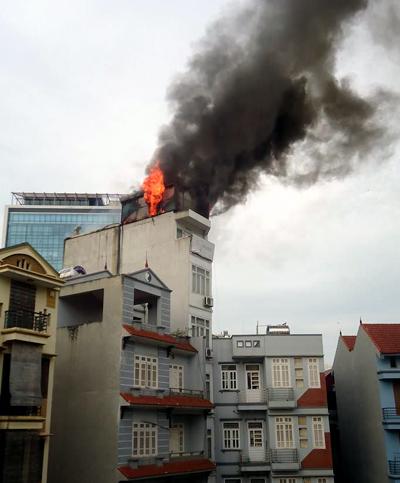 Lửa ngùn ngụt bốc lên từ tum tòa nhà. (Ảnh: độc giả Bùi Kim Xuyến)
