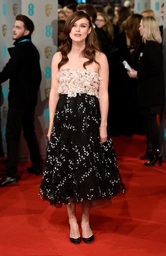 Bà bầu Keira Knightley khoác trên mình toàn thương hiệu đẳng cấp. Chiếc váy điệu đà cô mặc là một thiết kế trong BST mới của Giambattista Valli. Cô còn diện giày thiết kế của Paul Andrew, túi xách của Judith Leiber và trang sức của hãng Chanel.
