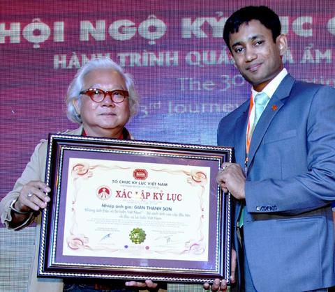 Tiến sĩ Biswaroo Roy Chowdhury, Giám đốc Tổ chức Kỷ lục Thế giới tại châu Á trao bằng chứng nhận Kỷ lục Việt Nam lần thứ 4 cho Giản Thanh Sơn (Ảnh: Nguyễn Thanh Minh).