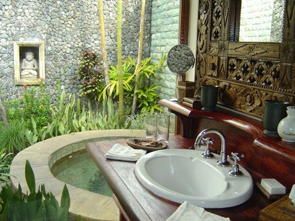Bồn tắm hình bán nguyệt với những bức tường ốp đá nhỏ nhắn, xung quanh bao bọc bởi cây cối cùng nội thất đi kèm tiện nghi, sang trọng.