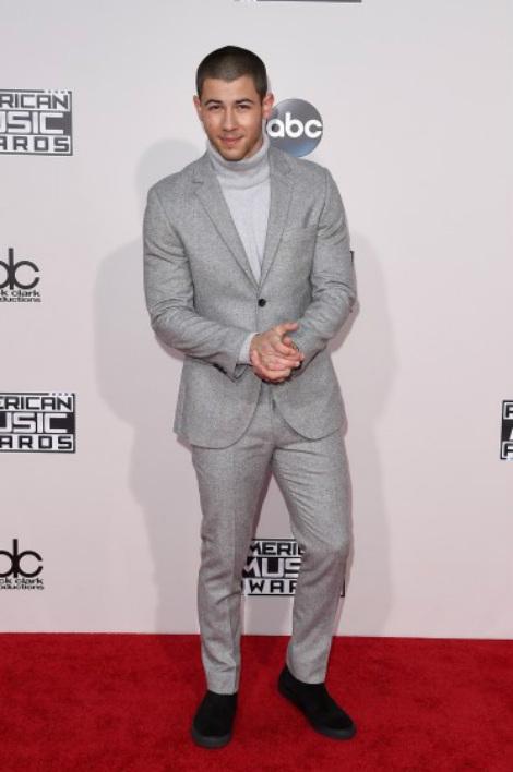 Nick Jonas kín cổng cao tường với trang phục gam màu bạc.