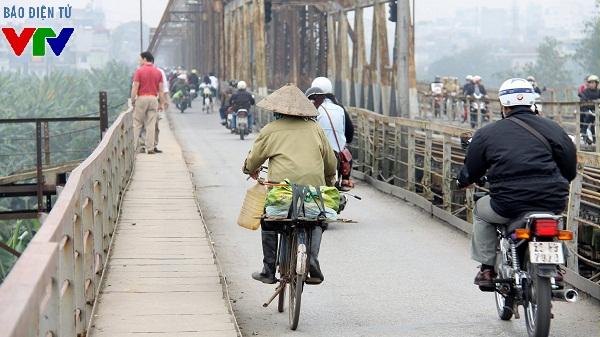 Người phụ nữ với chiếc xe đạp cũ kỹ trên cầu Long Biên trong đợt gió mùa đầu tiên của Hà Nội những ngày vừa qua