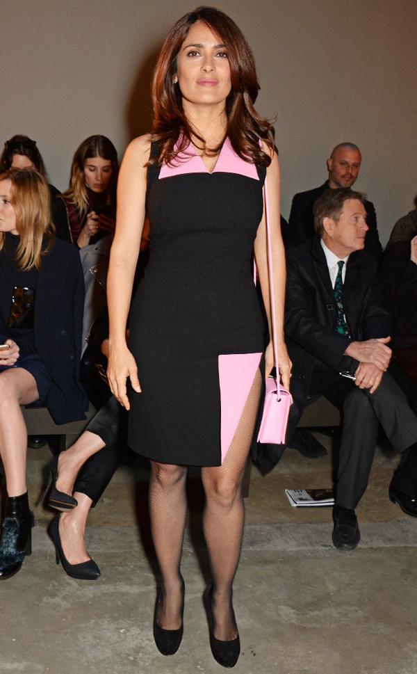 Nữ diễn viên Salma Hayek mặc chiếc váy đen - hồng với kiểu dáng ấn tượng, phụ kiện đi kèm là túi xách hồng hợp tông màu váy.
