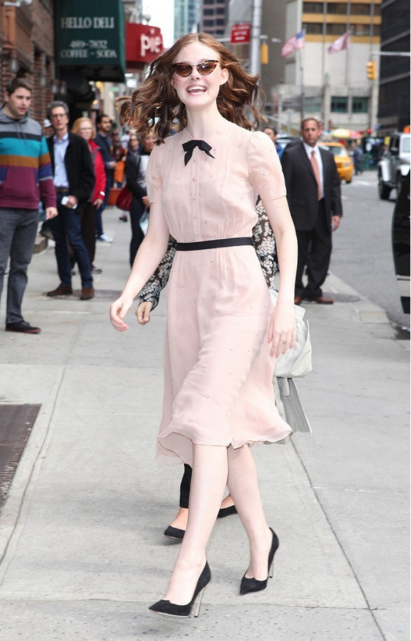 Elle nữ tính trên đường phố với váy midi (dài đếp bắp chân) bằng chất liệu lụa mềm mại trên tông màu hồng nhạt và kính mắt mèo gọng đồi mồi thời thượng.