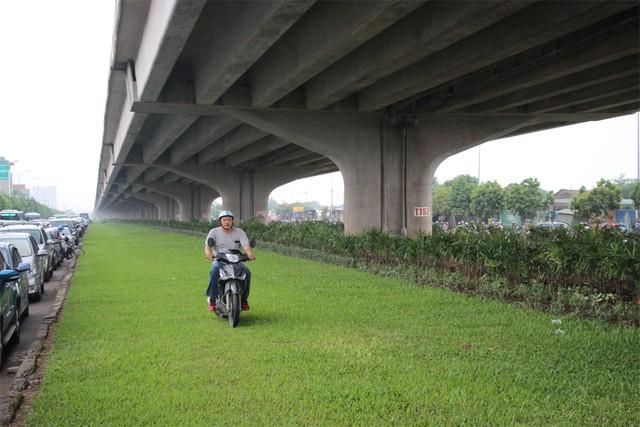 Nhiều xe máy lao lên cả thảm cỏ dưới gầm đường trên cao để đi.