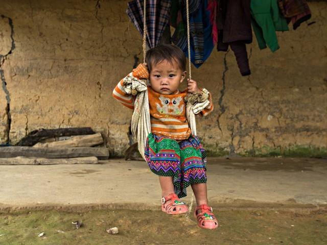 Một em bé người H'mong chơi một mình trước sân nhà.