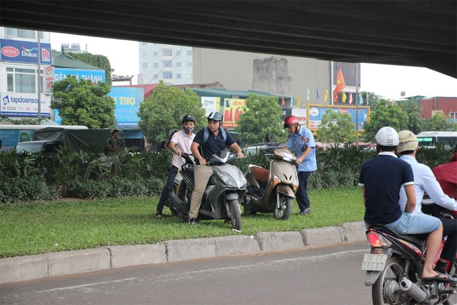 Cùng nhau đưa xe máy sang bên kia đường.