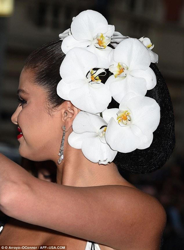 Mái tóc của cô được tô điểm bằng những bông hoa phong lan trắng tinh khôi