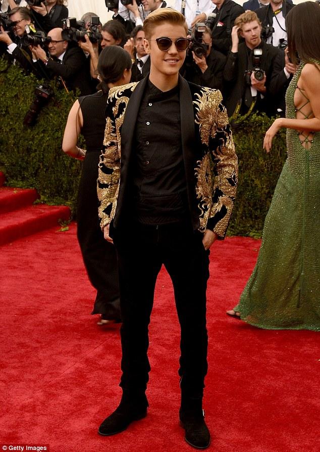 Nam ca sĩ điển trai khoác lên mình bộ vest mang họa tiết hình rồng châu Á được thêu bằng những sợi chỉ vàng sang trọng.